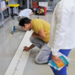 Un rouleau d'écriture qui se déroule au sol pour écrire les uns après les autres.